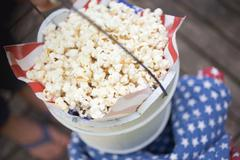 Hand holding wooden bucket full of popcorn (4th of July, USA) Stock Photos
