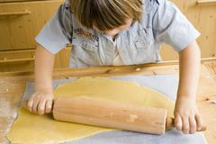 Child rolling out dough Stock Photos