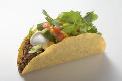Taco with mince, avocado, sour cream and coriander leaves Stock Photos
