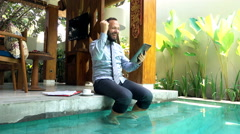 Successful businessman with tablet computer by pool in outdoor villa, slow motio Stock Footage