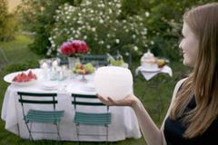 Woman holding windlight in front of table laid in garden Stock Photos