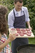 Man holding raw burgers over barbecue, woman holding iced tea Kuvituskuvat