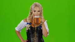 Bavarian woman drinking a beer glass showing thumbs up and winking. Green screen Stock Footage