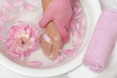 Woman washing her foot with pink peeling glove Stock Photos