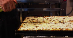 Pizza chef sprinkling olive oil on pan of pizza Stock Footage