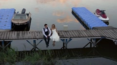 Happy wedding couple on jetty Stock Footage