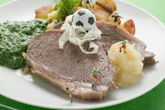 Boiled beef with accompaniments and football figures Stock Photos