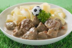 ZŸrcher Geschnetzeltes (veal dish) with ribbon pasta & toy football Stock Photos