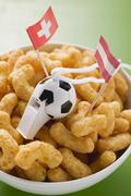 Peanut puffs with football whistle and flags in bowl Stock Photos