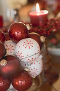 Assorted Christmas tree baubles in front of red candle Stock Photos