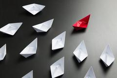 Leadership concept illustrated with paper ships Stock Photos
