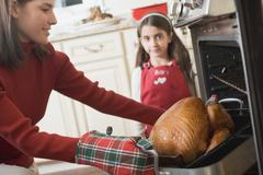 Young woman taking turkey out of oven, girl in background Stock Photos