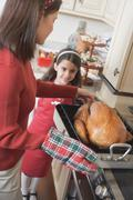 Young woman putting turkey on cooker, girl in background Stock Photos