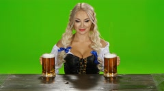 Bavarian girl takes on the table two glasses of beer. Green screen Stock Footage