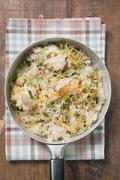 Pan-cooked rice and fish dish with lemon zest from above Stock Photos