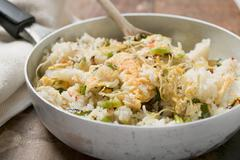Pan-cooked rice and fish dish with lemon zest Stock Photos