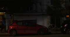 In evening city down road passing cars, motorcyclist, people walking around Stock Footage
