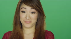 Young Asian woman awkwardly smiling, on a green screen background Stock Footage