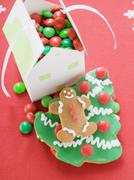 Christmas biscuits & paper house full of chocolate beans Stock Photos