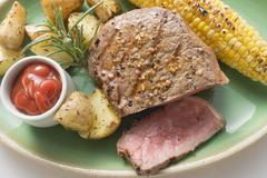 Peppered steak with corn on the cob, roast potatoes & ketchup Stock Photos