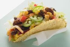 Taco filled with sweetcorn and beans on paper napkin Stock Photos