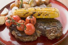 Grilled steak with corn on the cob, cherry tomatoes, potatoes Stock Photos