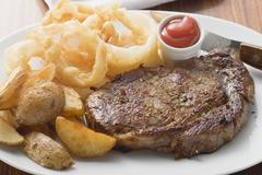 Rib-eye steak with onion rings, ketchup and potato wedges Stock Photos