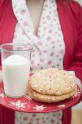 Woman holding Christmas cookies and glass of milk on plate Stock Photos