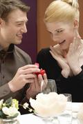 Man giving woman diamond ring over romantic meal Kuvituskuvat