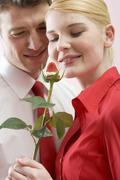 Romantic couple with chocolate-dipped strawberry on rose stalk Stock Photos