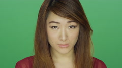 Young Asian woman looking sad, on a green screen background Stock Footage