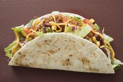 Taco filled with mince & cheese on brown background Stock Photos