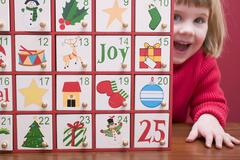 Small girl peeping out from behind Advent calendar Stock Photos