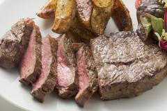 Beef steak with potato wedges and salad Stock Photos