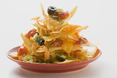 Nachos with cheese, olives, chilli rings & ketchup on plate Stock Photos