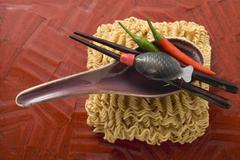 Egg noodles, soup spoon, soy sauce and chillies (Asia) Stock Photos