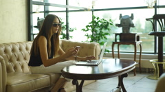 Beautiful businesswoman sitting on a leather couch and working at a computer Stock Footage