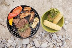Meat & vegetables on barbecue, accompaniments in bowl Stock Photos