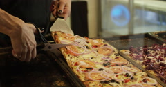 Caucasian waitress cutting pizza sliced with scissors in display case Stock Footage