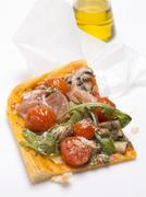 Slice of pizza topped with ham, tomatoes, mushrooms, rocket Stock Photos