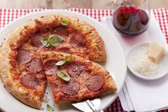 Pizza with salami and basil; one slice of the pizza is on a pizza shovel Stock Photos