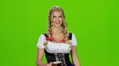 Girl in bavarian costume blows on beer foam. Slow motion. Green screen Stock Footage