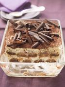 Tiramisu topped with chocolate curls, in a glass dish, part already served Kuvituskuvat