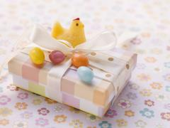 An Easter parcel with a fondant chick and sugar eggs Stock Photos