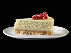 A piece of New York cheesecake with redcurrants Stock Photos