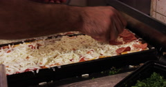 Pizza chef putting pepperoni on pan of pizza Stock Footage