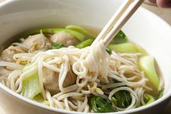 Hand Twirling Noodles from Shanghai Noodle Meatball Soup onto Chopsticks Stock Photos