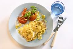 Baked cod, garnished with tomatoes and leeks Stock Photos