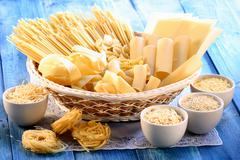 Various types of pasta in basket and bowls Stock Photos