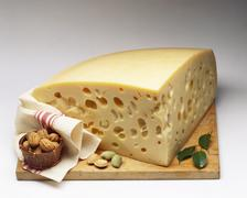 Emmental with almonds and walnuts on wooden board Stock Photos